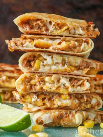 Tall stack of cheesy refried bean quesadillas on a blue board next to corn chips, lime wedges and kernels of corn.