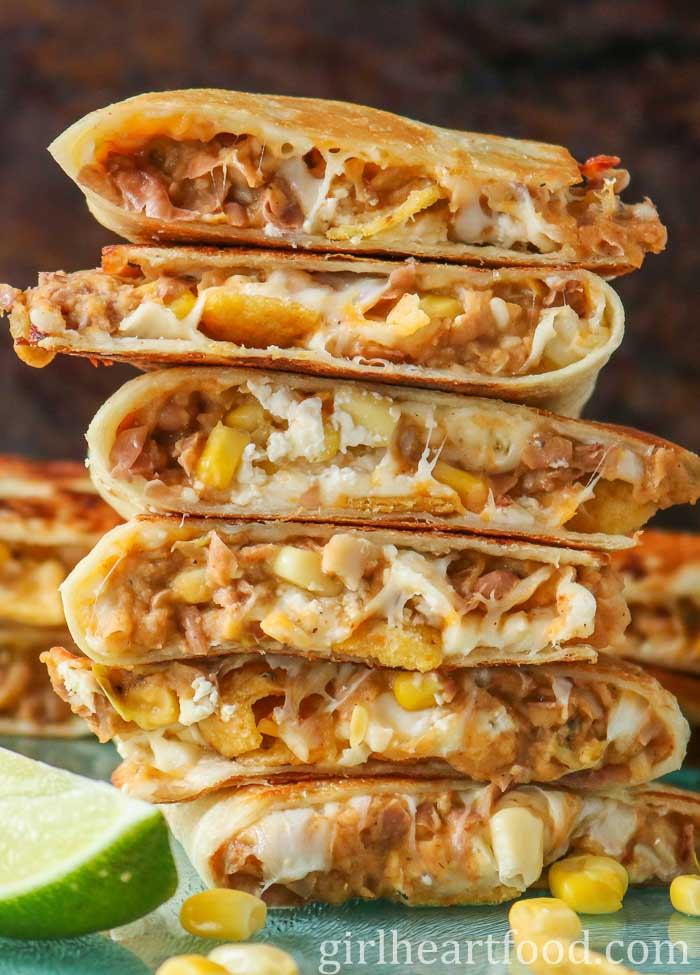 Tall stack of quesadillas made with refried beans, corn, cheese and chips on a blue board.