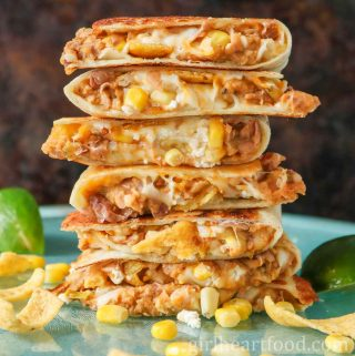 Tall stack of cheesy refried bean quesadillas with corn next to lime wedges.