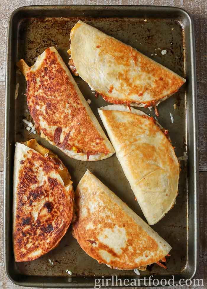 Crispy quesadillas on a baking sheet.