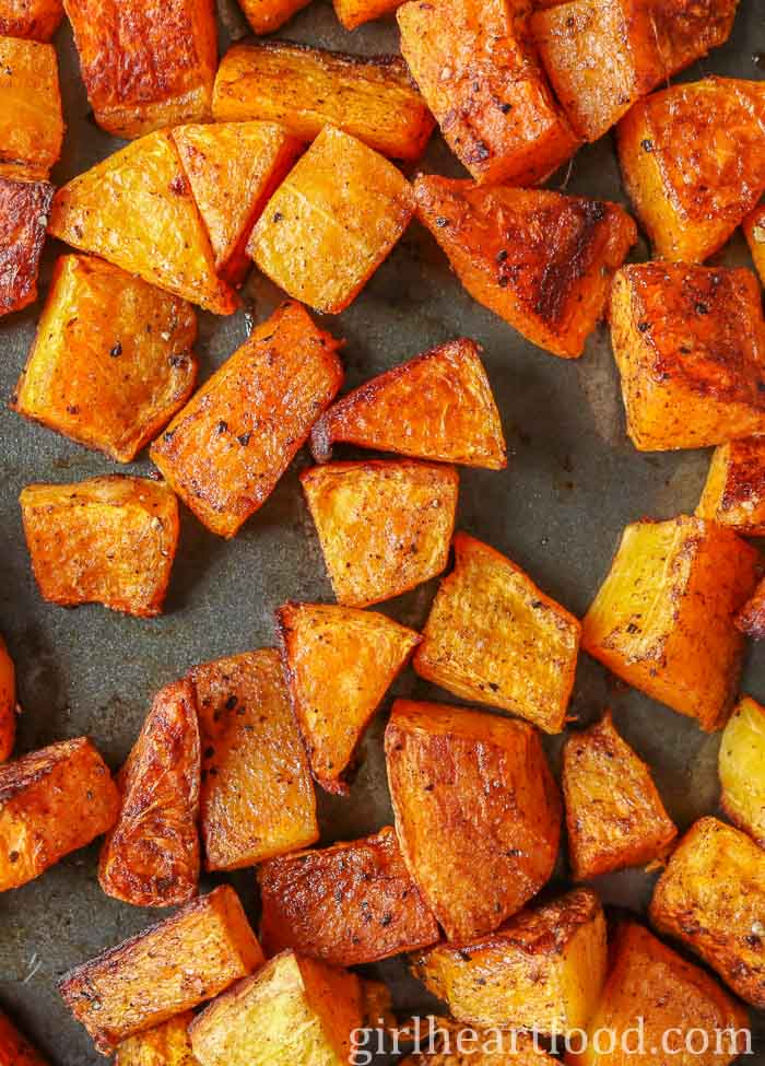 Chunks of oven-baked butternut squash on a sheet pan.