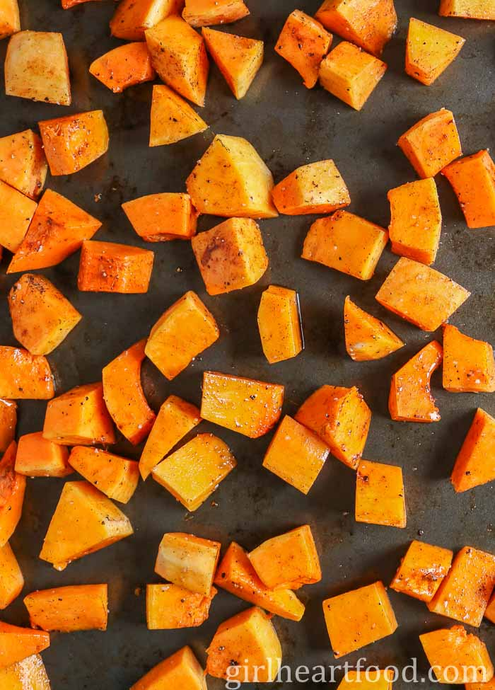 Chunks of butternut squash on a sheet pan before being roasted.
