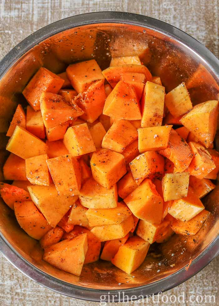 Cubes of seasoned butternut squash in a stainless steel bowl.