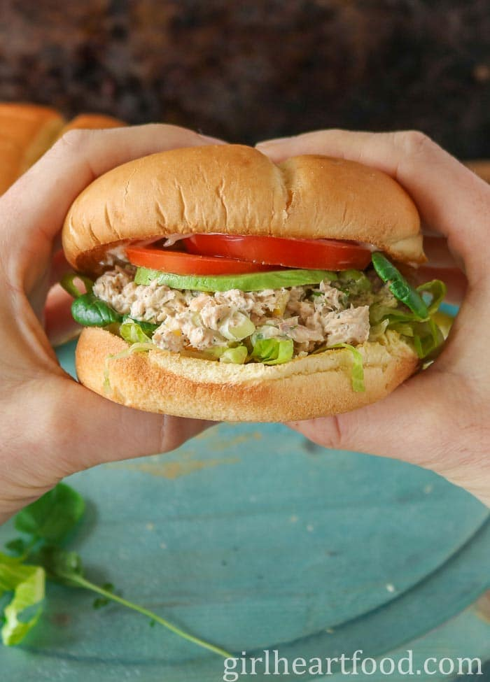 Two hands holding a salmon salad sandwich.