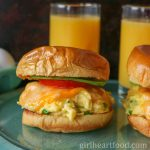 Cheesy scrambled egg breakfast sandwich on a brioche with tomato and avocado.