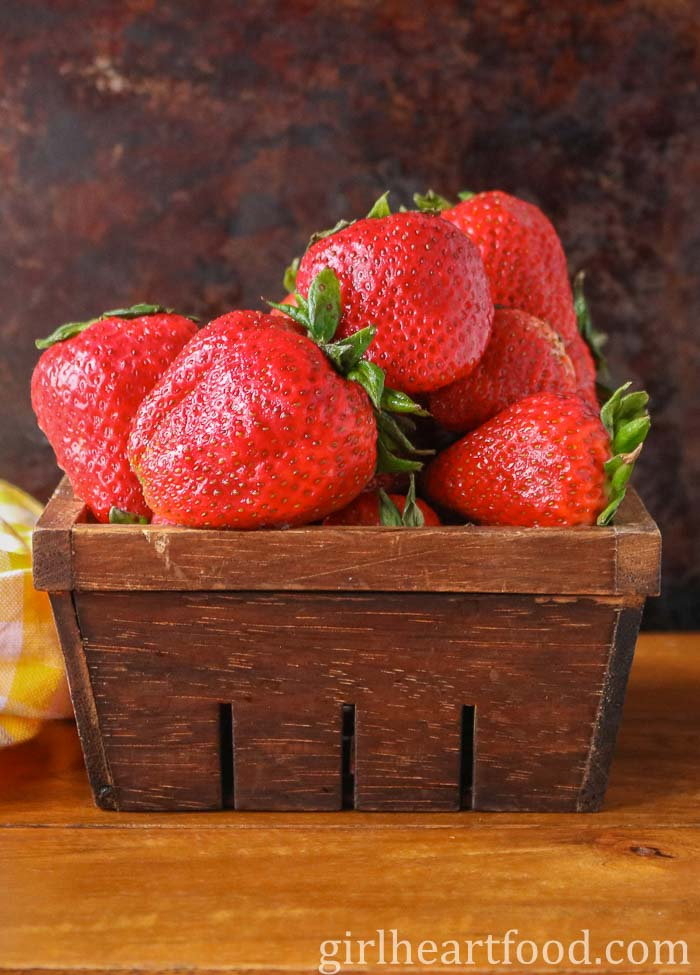 Fresh strawberries in a brown wooden carton.