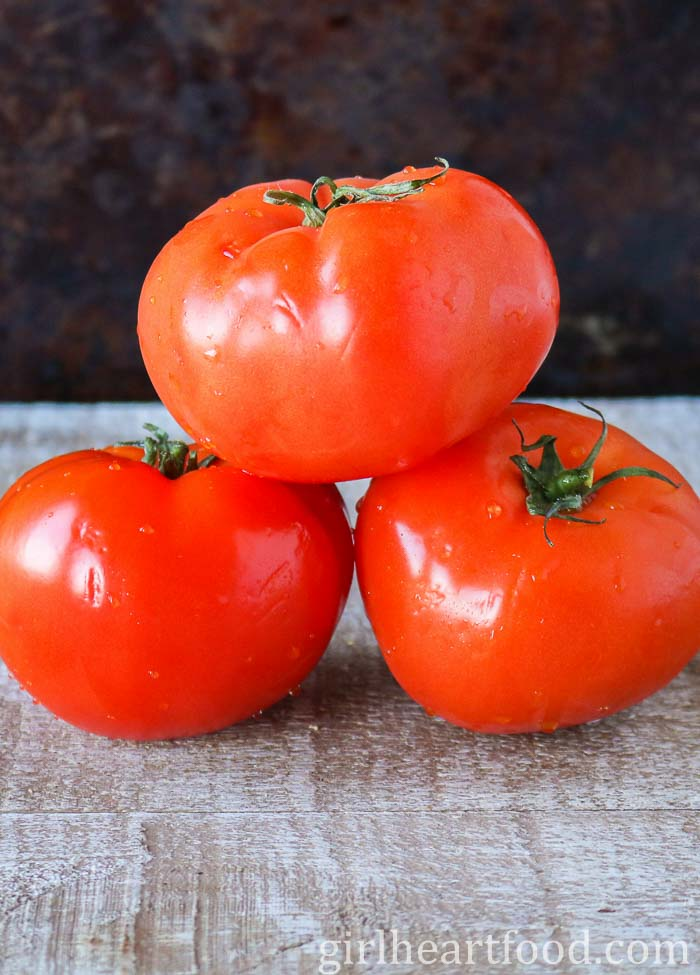 Three tomatoes stacked on a wooden board.