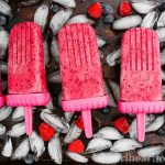 Frozen berry pops on a tray with ice cubes and berries.
