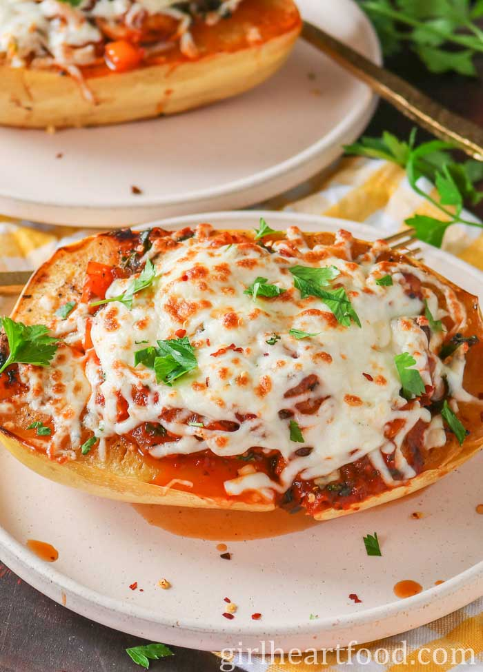 A vegetarian stuffed spaghetti squash boat topped with mozzarella cheese and parsley.