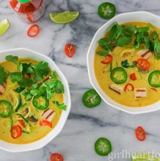 Two bowls of curry vegetable tofu soup garnished with cilantro and hot peppers.