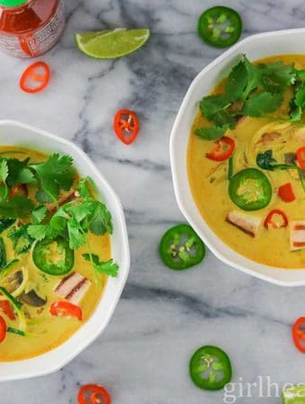 Two bowls of curry vegetable soup garnished with cilantro and hot peppers.