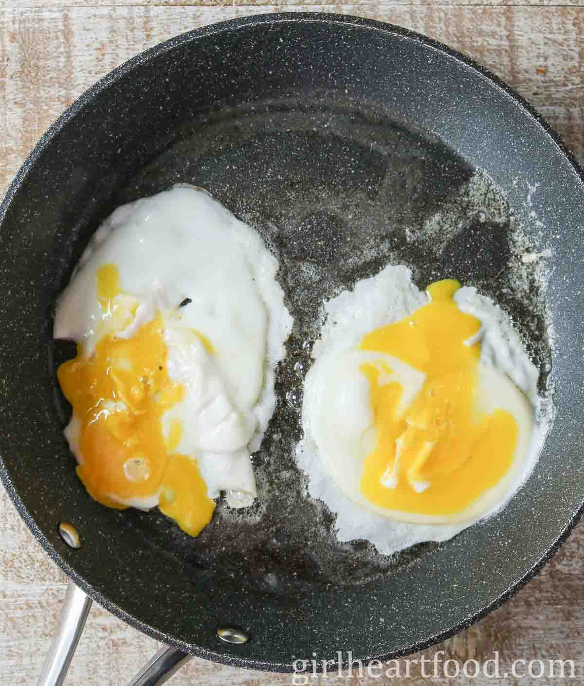 Two eggs frying in a non stick pan with the yolks broke.