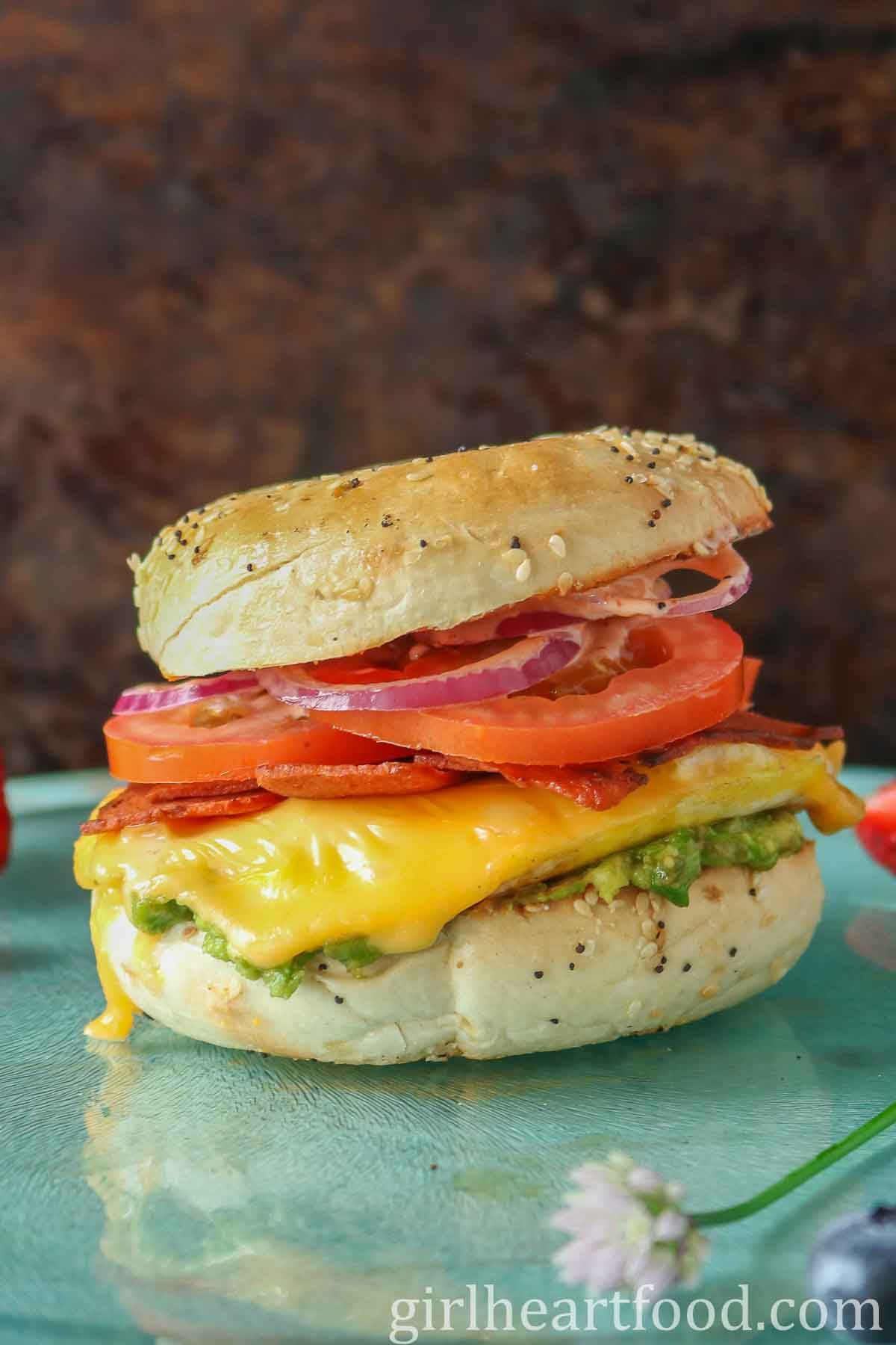 Cheesy bagel breakfast sandwich on a blue board.