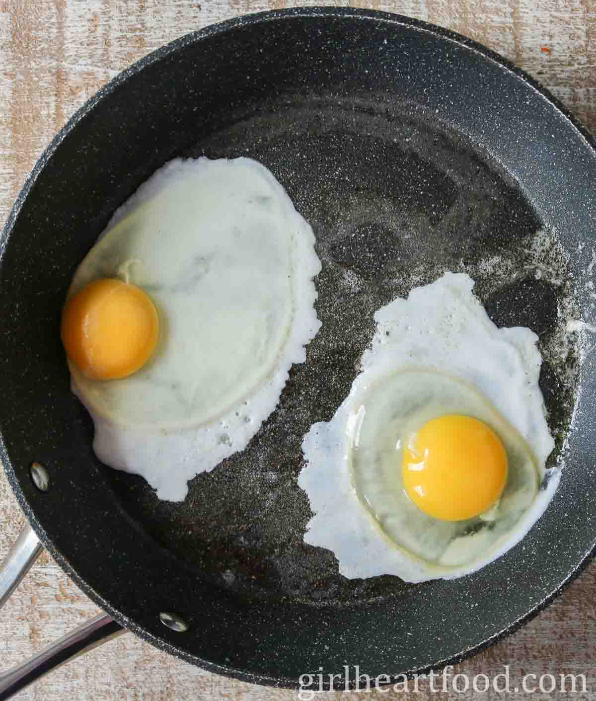 Two eggs frying in a non stick pan.