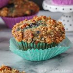Blueberry muffin wrapped in two muffin liners.