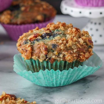 A blueberry muffin wrapped in a teal muffin liner.