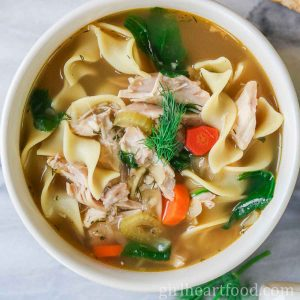 Bowl of homemade chicken noodle soup garnished with dill.