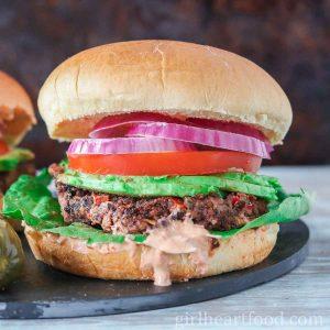 Vegan black bean burger garnished with onion, tomato, avocado, lettuce and sauce.