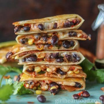 Tall stack of cheesy black bean and corn quesadillas.