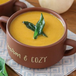 Bowl of creamy butternut squash sweet potato soup garnished with crispy sage leaves.