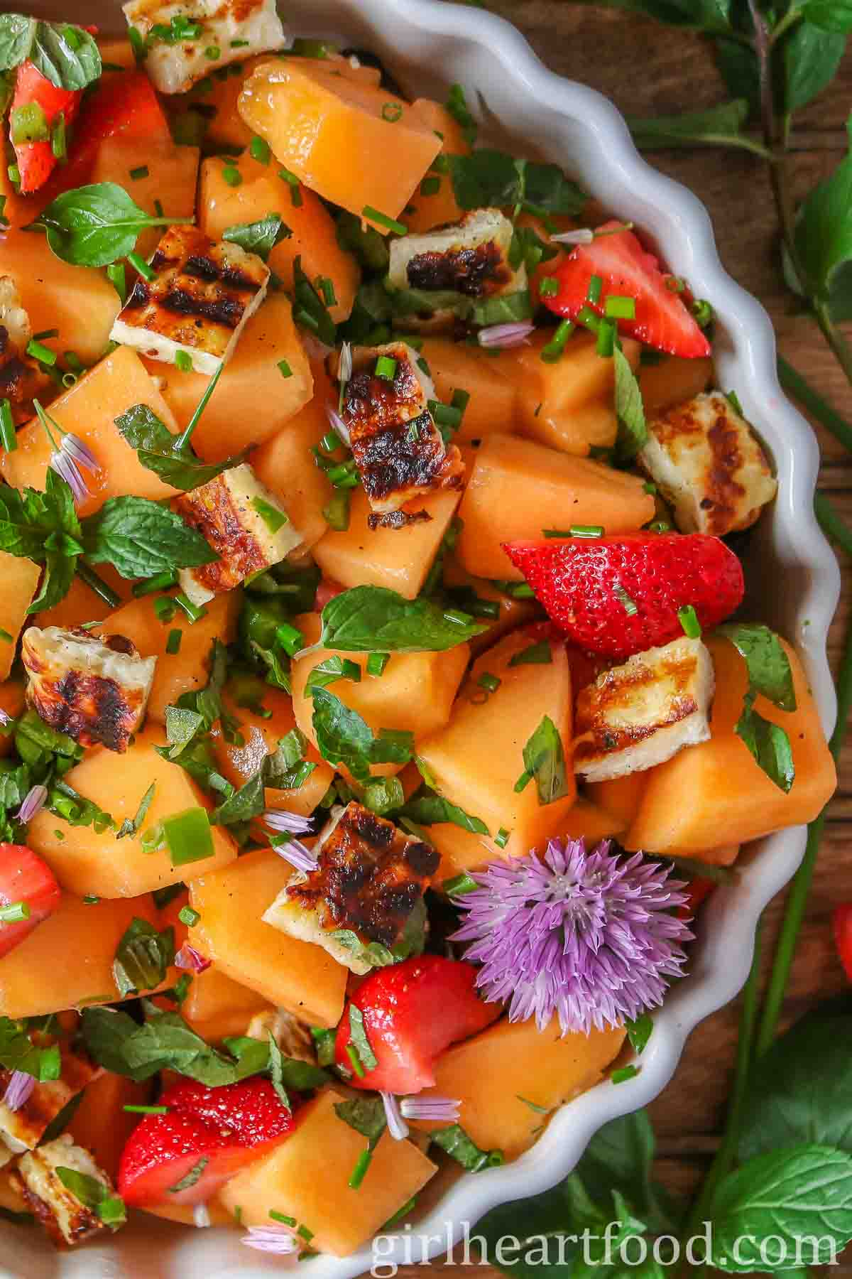 Close up of a cantaloupe salad recipe garnished with a chive flower.