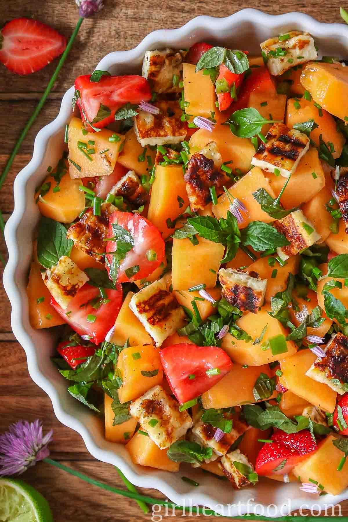 Close up of a dish of cantaloupe fruit salad with grilled halloumi cheese.