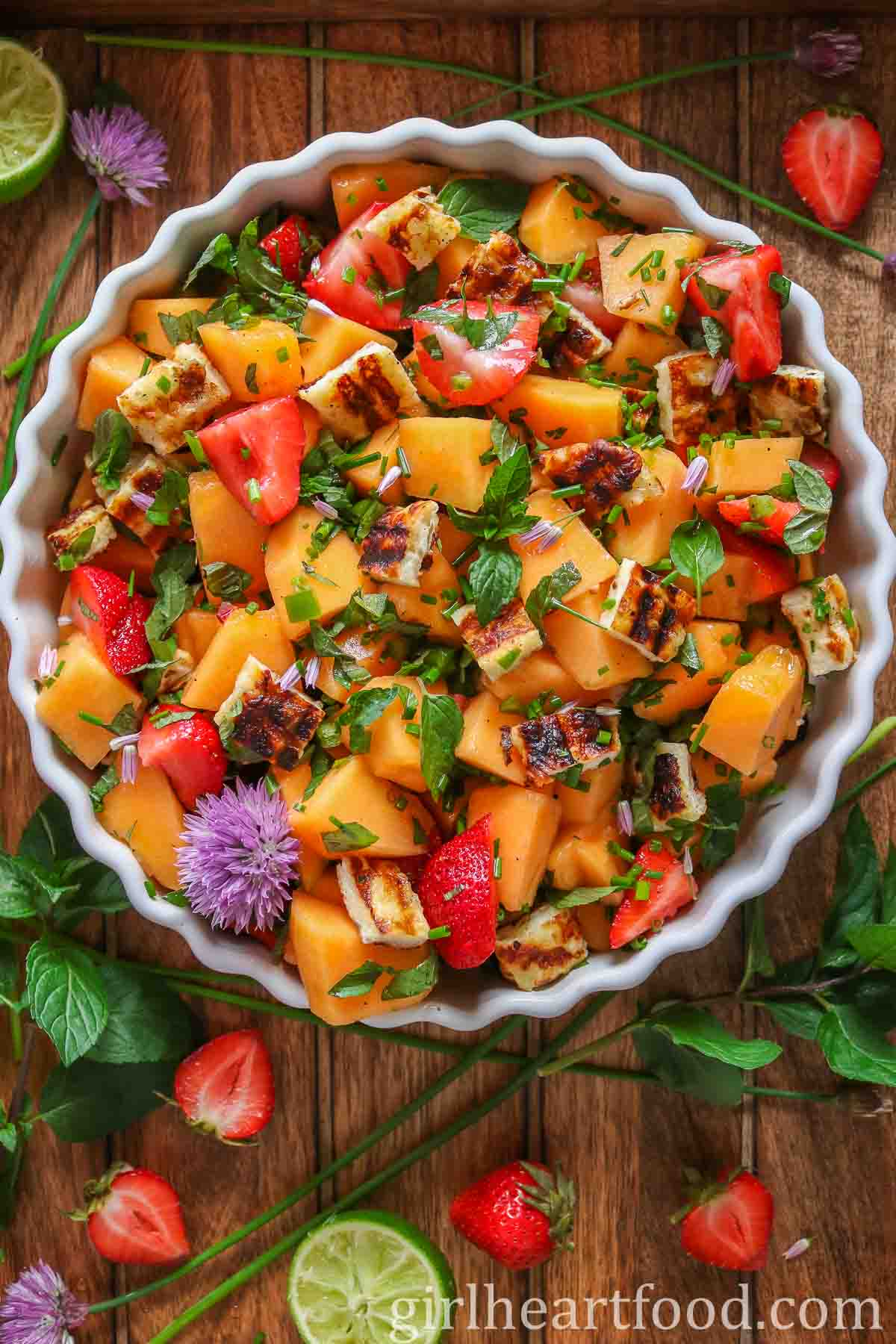 Overhead shot of a white round dish of cantaloupe salad garnished with mint and chives.
