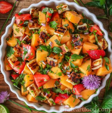 Round dish of a cantaloupe fruit salad with grilled halloumi cheese.