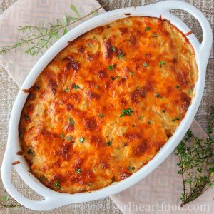 Oval casserole dish of cheesy scalloped potatoes garnished with fresh thyme.