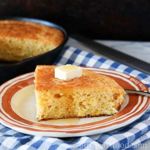 A slice of cornbread with a dab of butter and honey over top on a plate.