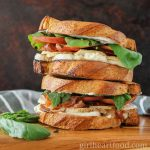 Two chicken and prosciutto sandwiches stacked on top of each other, alongside some fresh basil.