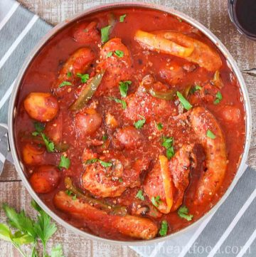 Large round pan of chicken, sausage and peppers in tomato sauce and garnished with parsley.