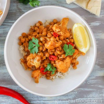 Bowl of chickpea cauliflower curry over rice and garnished with chili, cilantro and lemon wedge.