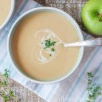 Bowl of creamy parsnip apple soup garnished with chives and cream.