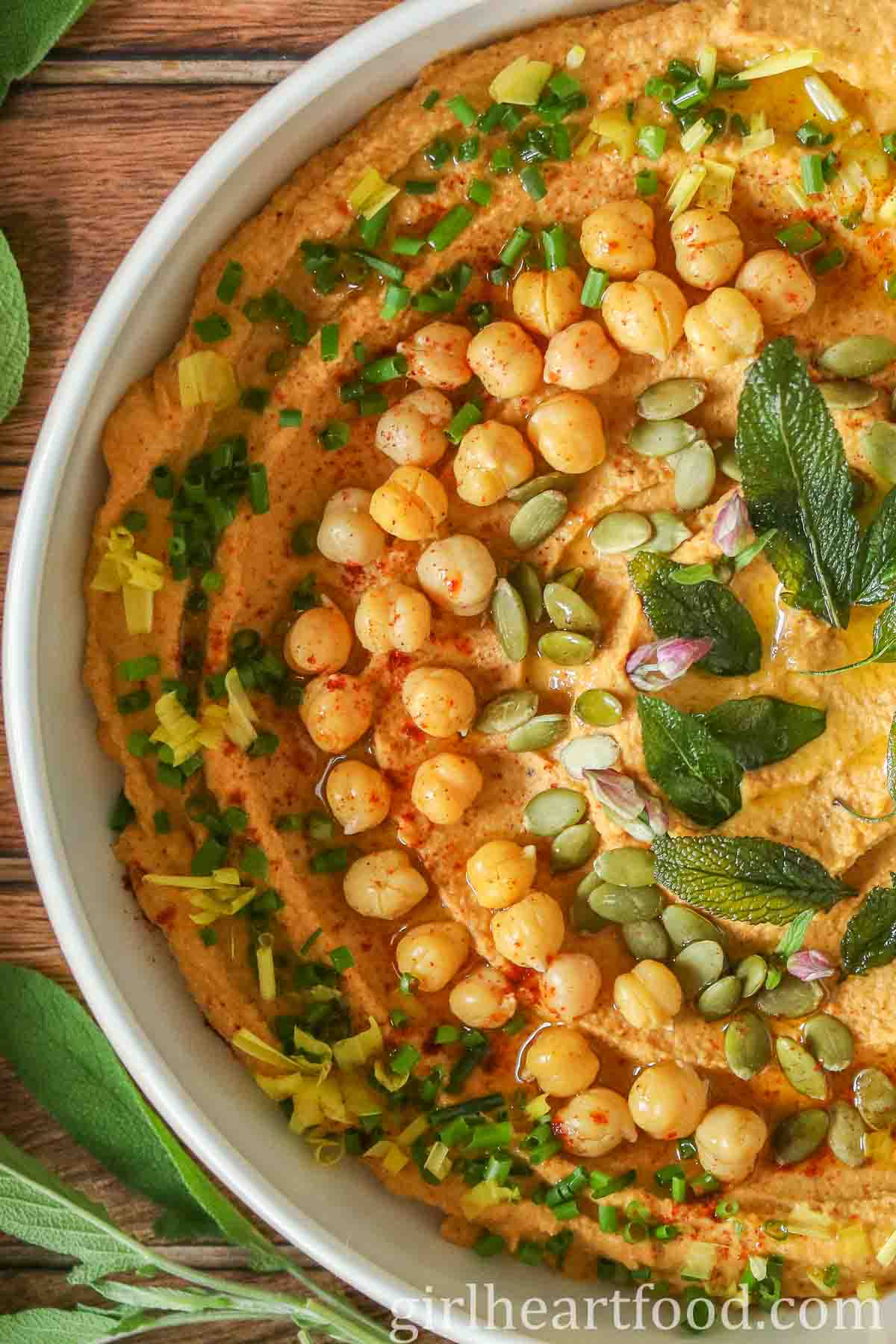 Close-up of a bowl of pumpkin hummus garnished with herbs, chickpeas, oil and pumpkin seeds.