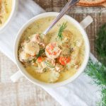 White bowl of creamy seafood chowder with dill.