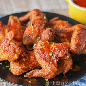 Crispy baked chicken wings with chive garnish on a black plate.