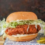 Crispy fried chicken burger on a bun with shredded lettuce and mayo.