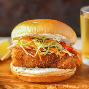 Crispy fish burger with homemade coleslaw and tartar sauce on a wooden board.