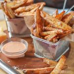 Two stainless steel baskets of crispy potato wedges garnished with parmesan and alongside a dish of dipping sauce.