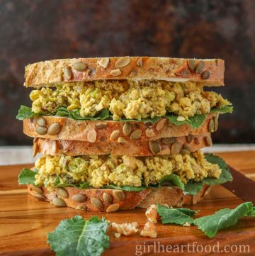 Two curried chickpea salad sandwiches with baby kale stacked on top of each other.