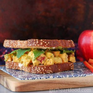 Curry chicken salad sandwich with apple next to an apple and carrot sticks.