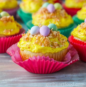 An Easter cupcake topped with yellow frosting, toasted coconut and candy wrapped in a pink muffin liner.