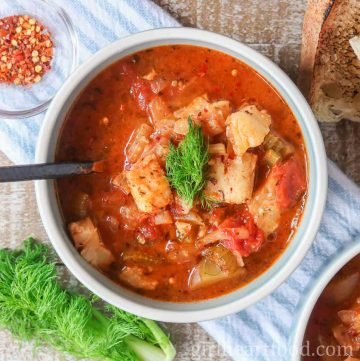 Bowl of a tomato based fish stew garnished with fennel.