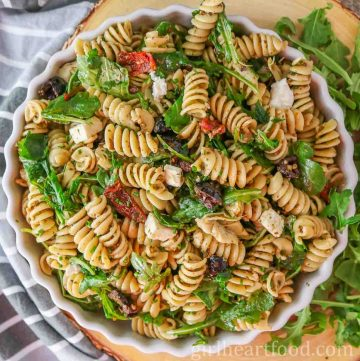 Bowl of Mediterranean pesto pasta salad next to a tea towel and arugula.