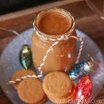 Mason jar of gingerbread coffee creamer on a plate next to gingerbread cookies and festive holiday lights.