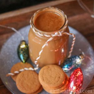 Jar of gingerbread coffee creamer, cookies and holiday lights on a silver plate.
