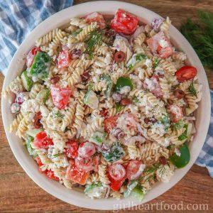 Large round dish of gluten-free Greek pasta salad tossed in a yogurt dressing.