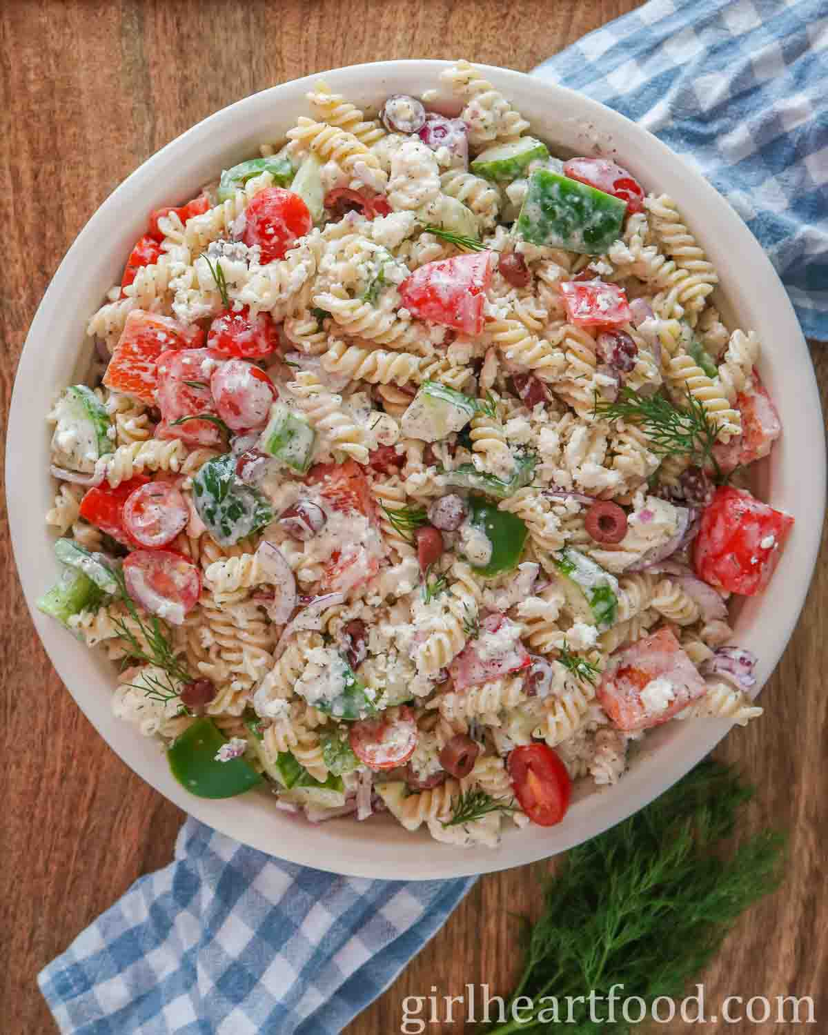 Large round dish of gluten free pasta salad with vegetables, feta, olives and creamy dressing.