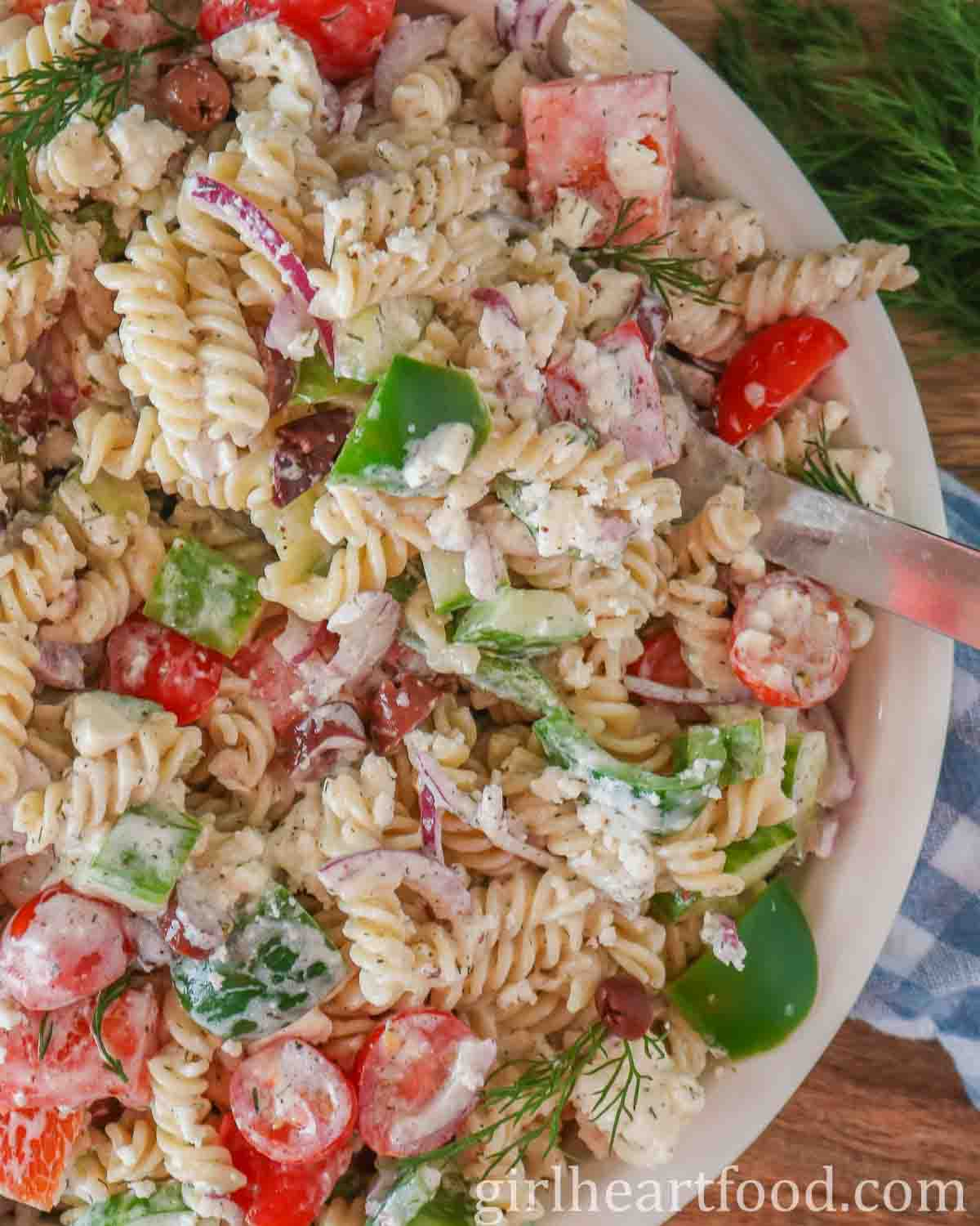 Close up of a dish of creamy Greek pasta salad with a steel spoon stuck into the salad.